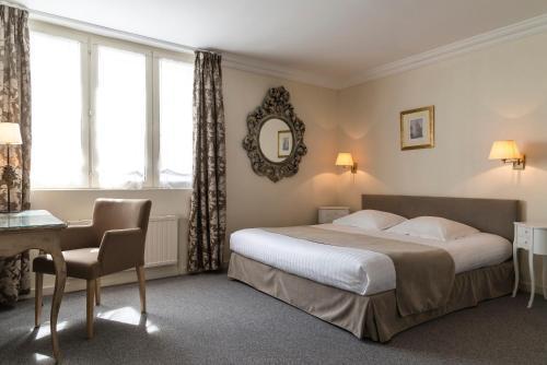 A bed or beds in a room at Najeti Hôtel de L'univers