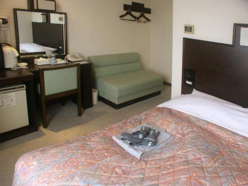 A bed or beds in a room at Takada Terminal Hotel