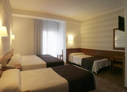 A bed or beds in a room at Hotel Costa Brava
