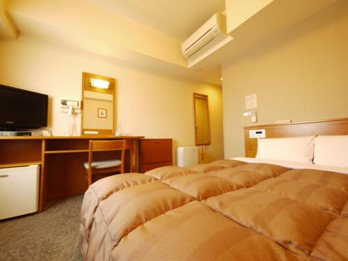 A bed or beds in a room at Hotel Route-Inn Fukaya Ekimae