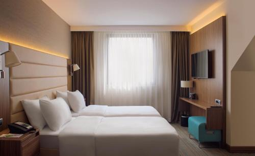 A bed or beds in a room at Courtyard by Marriott Belgrade City Center