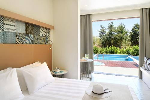A bed or beds in a room at Lindos Imperial Resort & Spa