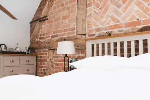 A bed or beds in a room at Tuppenhurst Barn