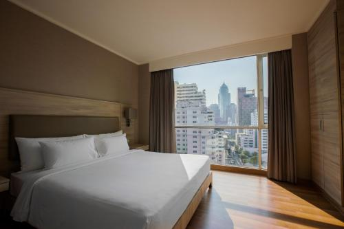 A bed or beds in a room at Adelphi Suites Bangkok