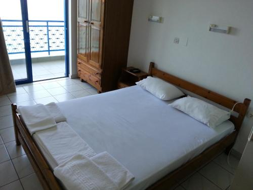 A bed or beds in a room at Angelos Hotel