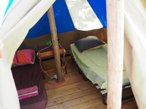 A bed or beds in a room at Les roulottes de Cambonis