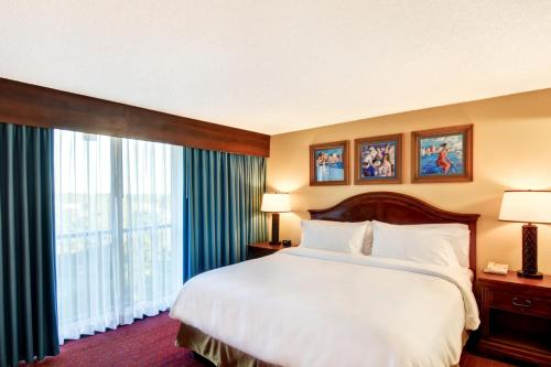 A bed or beds in a room at Embassy Suites Orlando - North
