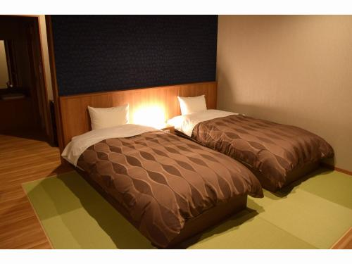 A bed or beds in a room at Hotel New Umeya