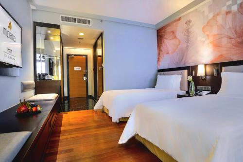 A bed or beds in a room at Impiana KLCC Hotel