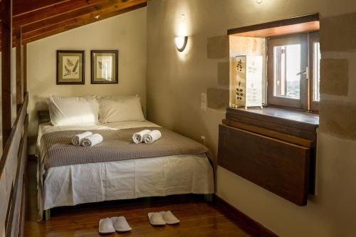 A bed or beds in a room at The Carob Tree Cottage