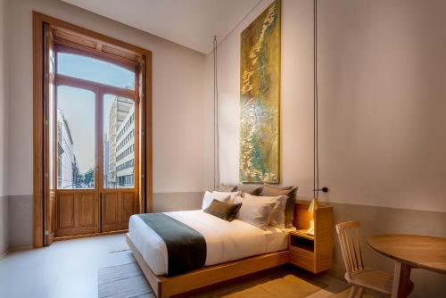 A bed or beds in a room at Umbral, Curio Collection By Hilton