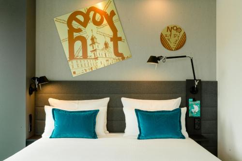A bed or beds in a room at Motel One Warsaw-Chopin