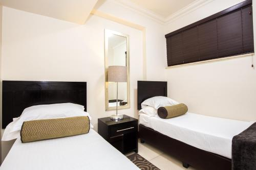 A bed or beds in a room at Belaire Suites Hotel
