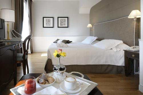 A bed or beds in a room at Grand Hotel Santa Lucia
