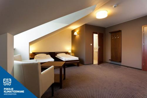 A bed or beds in a room at Hotel Podzamcze