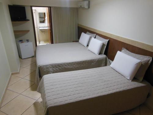 A bed or beds in a room at Alfa Plaza Hotel