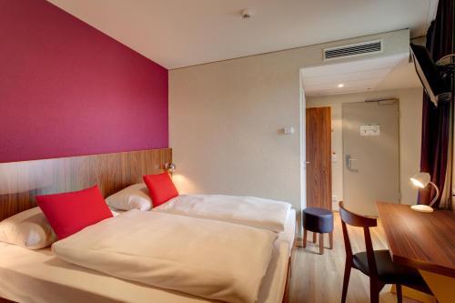 Een bed of bedden in een kamer bij MEININGER Hotel Frankfurt Main / Airport