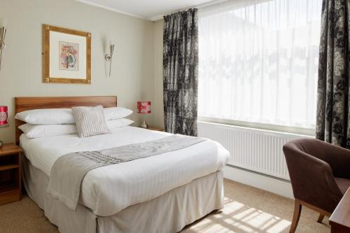 A bed or beds in a room at Alma Lodge Hotel