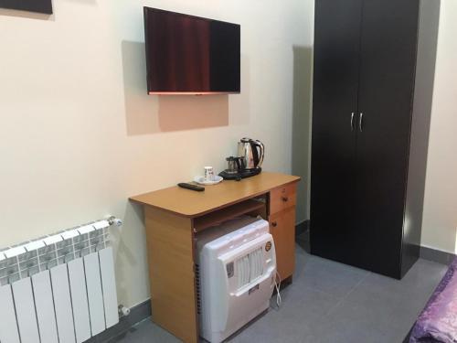 Uma TV ou centro de entretenimento em Alp Hotel