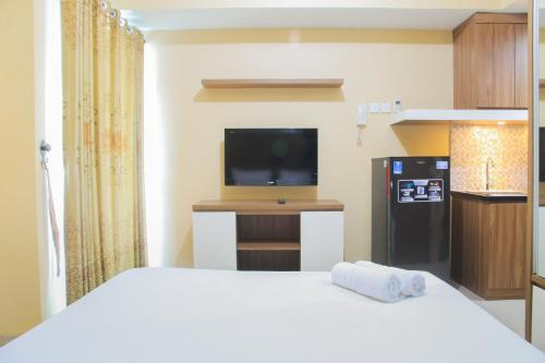 A television and/or entertainment center at Relaxing Studio @ Grand Dhika City Apartment By Travelio