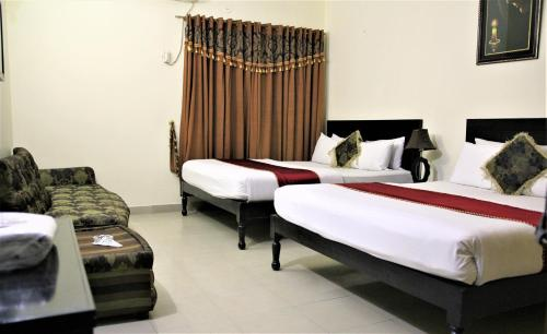 A bed or beds in a room at Tourist Inn Hotel