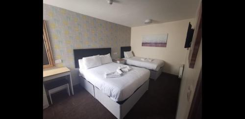 A bed or beds in a room at The Avenue Club and Lodge