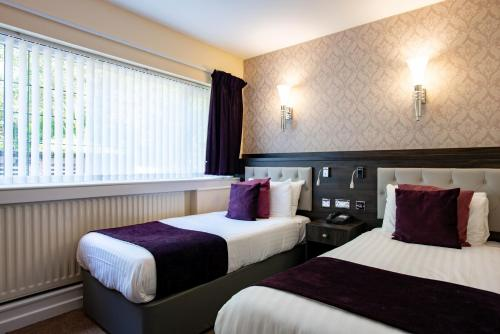 A bed or beds in a room at Southcrest Manor Hotel; BW Signature Collection