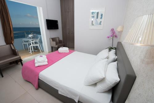 A bed or beds in a room at Astron Hotel