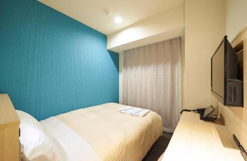 A bed or beds in a room at Sotetsu Fresa Inn Osaka Namba