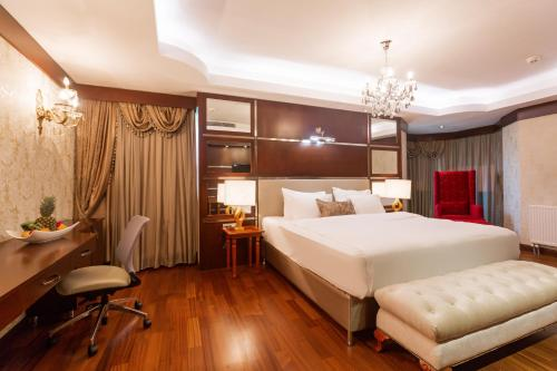 A bed or beds in a room at Dedeman Oskemen Tavros Hotel