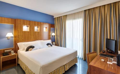A bed or beds in a room at Kalma Sitges Hotel