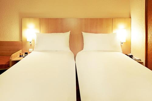 A bed or beds in a room at ibis Rambouillet