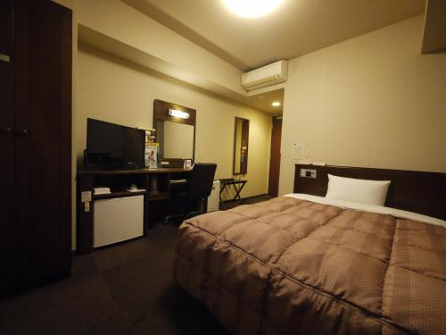 A bed or beds in a room at Hotel Route-Inn Hofu Ekimae