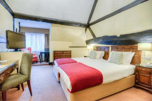 A bed or beds in a room at Mercure Stratford Upon Avon Shakespeare Hotel