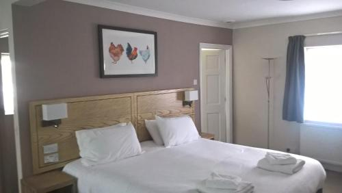A bed or beds in a room at Bear Inn, Somerset by Marston's Inns