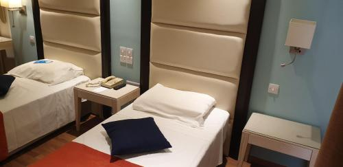 A bed or beds in a room at Castelli Hotel Nicosia
