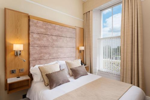 A bed or beds in a room at Invicta Hotel