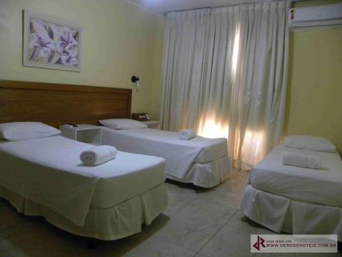 A bed or beds in a room at De Rose Palace Hotel