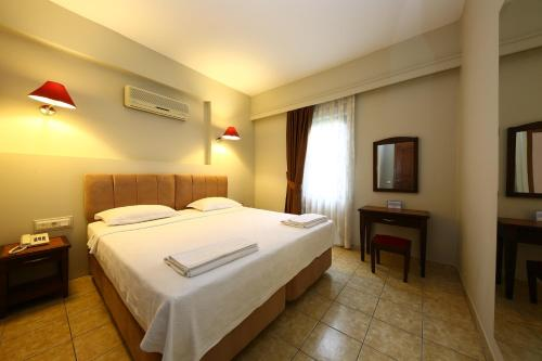 A bed or beds in a room at Mr. Dim Exclusive Apart Hotel