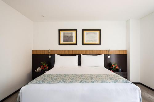 A bed or beds in a room at Madisson Inn Hotel & Luxury Suites