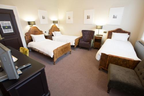 A bed or beds in a room at The White Hart Hotel Lincoln