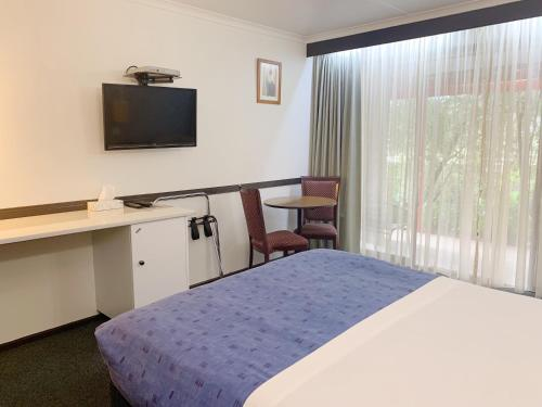 A bed or beds in a room at Statesman Motor Inn