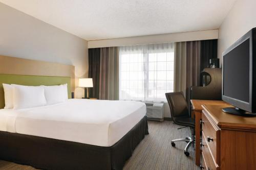 A bed or beds in a room at Country Inn & Suites by Radisson, Springfield, OH