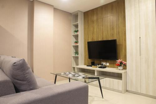 A television and/or entertainment center at Homey 1BR at Enviro Apartment Cikarang By Travelio