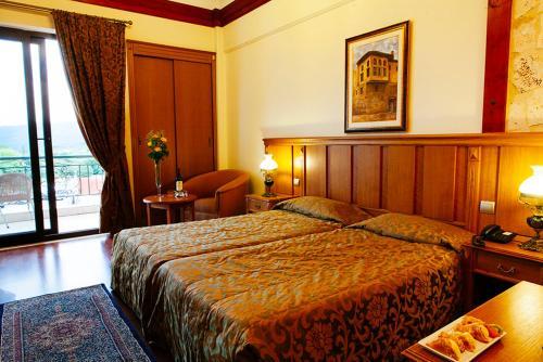 Ένα ή περισσότερα κρεβάτια σε δωμάτιο στο Ξενοδοχείο Αιγές Μέλαθρον