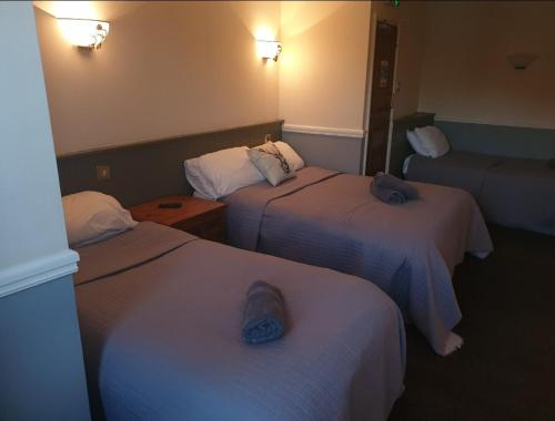 A bed or beds in a room at The Olde Swan Hotel