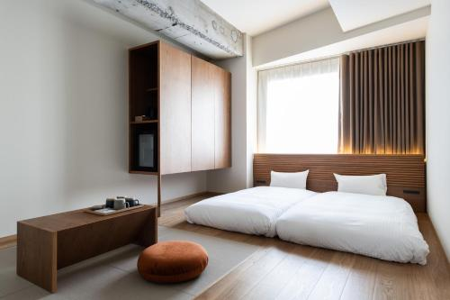 A bed or beds in a room at KIRO Hiroshima by THE SHARE HOTELS