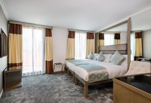 A bed or beds in a room at Atrium Hotel Heathrow