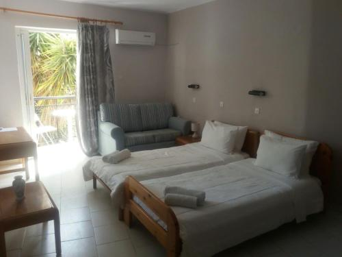 A bed or beds in a room at Pantheon Apartments Kos Town