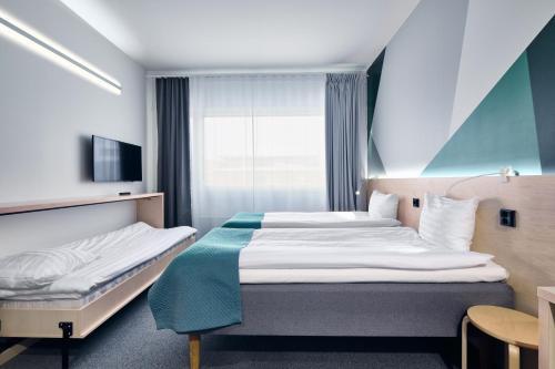 A bed or beds in a room at GreenStar Hotel Jyväskylä